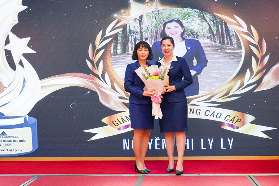 Phó tổng Kinh doanh Tiếp thị Lê Trần Bích Thùy trao hoa và cúp cho Giám đốc bán hàng cấp cao Nguyễn Thị Ly Ly